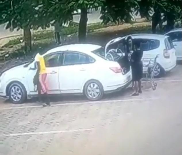 Young Man Caught On CCTV Camera Stealing From A Lady's Car While She Was Offloading Goods From Her Trunk